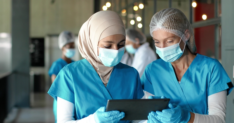 Multi ethnic women doctors in medical masks and gloves walking in hospital and talking about diagnosis. Mixed-races females medics consulting and discussing illness. Covid-19 Nurses with tablet device Royalty-Free Stock Footage #1060503760