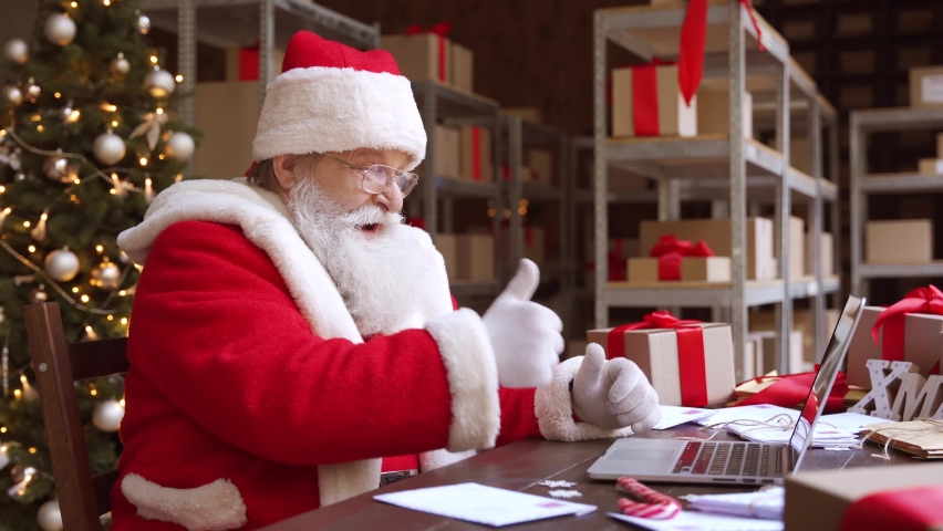 Santa Claus video calling on laptop talking greeting on Merry Christmas, Happy New Year in virtual video online chat meeting on computer sitting at workshop table sending present gift on xmas eve. Royalty-Free Stock Footage #1060506847
