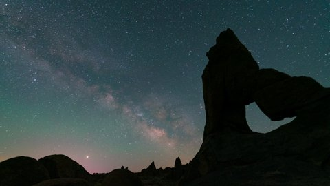 Time lapse tracking shot of Milky Way galaxy over Lady Boot Arch in Alabama Hills, California