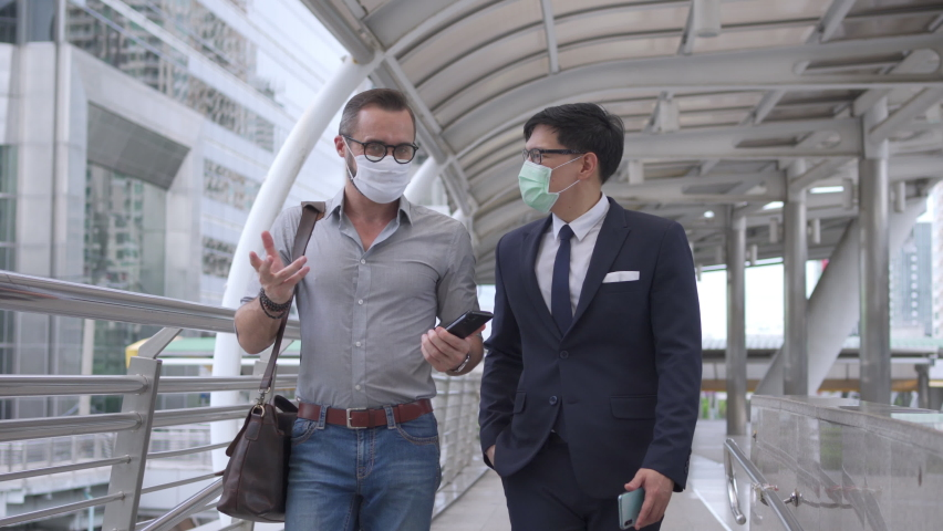 Business people Caucasian with Asian man office worker colleague wearing face mask for protect covid-19 virus walking together on office district and discussing business project with using smartphone. Royalty-Free Stock Footage #1060512763