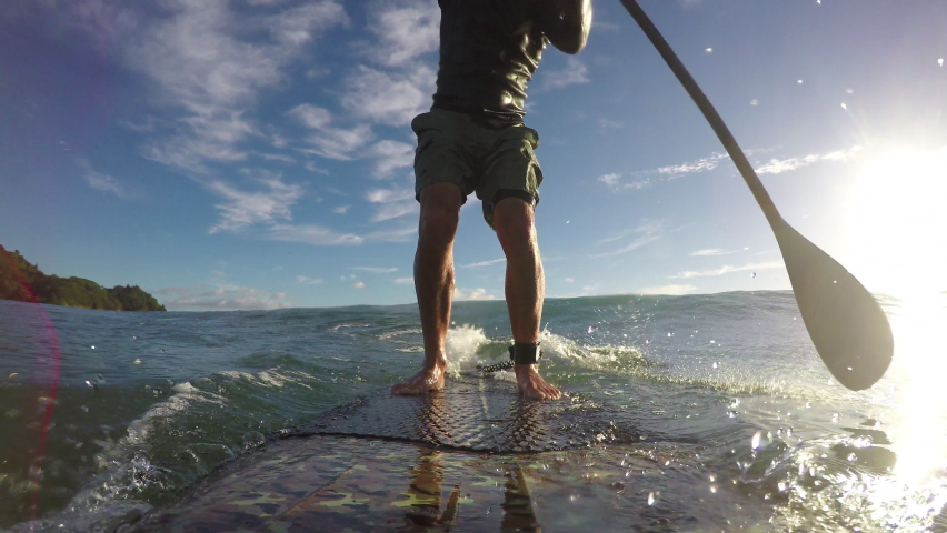 Standup paddle board surfing early morning at Waihi beach, New Zealand