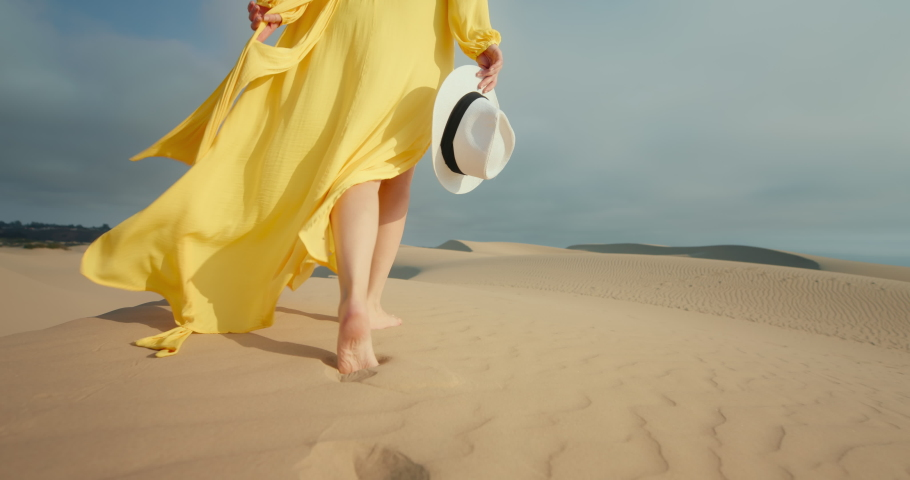 Close-up of woman in flattering yellow dress walking barefoot by wavy sand dunes in desert landscape. 4K Slow Motion golden sunset light highlighting model. Slim female legs with nature background Royalty-Free Stock Footage #1060520746