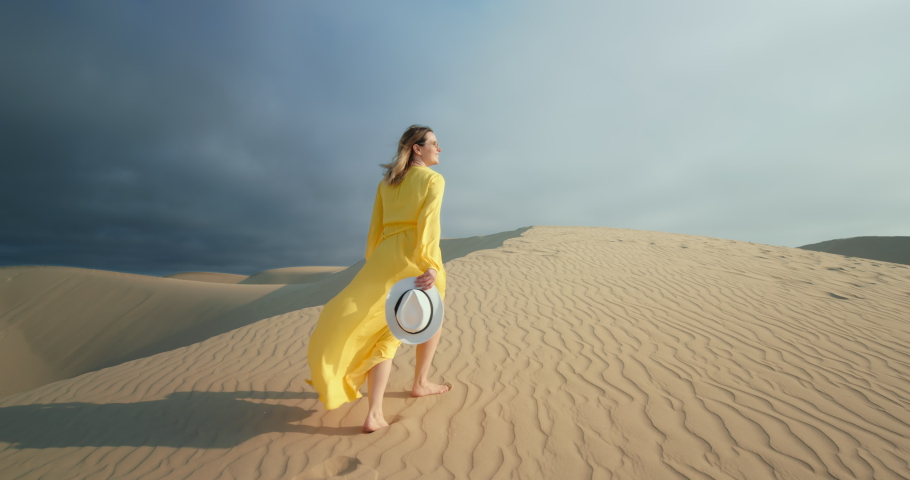 Cinematic slow motion of woman walking by sand dune. Barefoot female traveler in waving on the wind dress by the rippled sand desert surface with dark grey cloud on background. 4K Scenic nature  Royalty-Free Stock Footage #1060520752