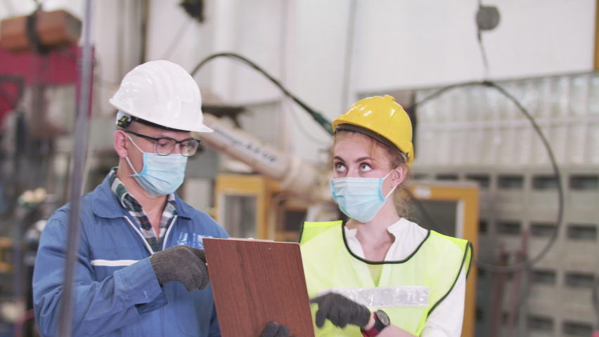 New normal of working. Portrait engineer and supervisor wearing safety helmet and protection mask face protect dust and pandemic of virus covid-19 while working workplace or production line in factory Royalty-Free Stock Footage #1060525213