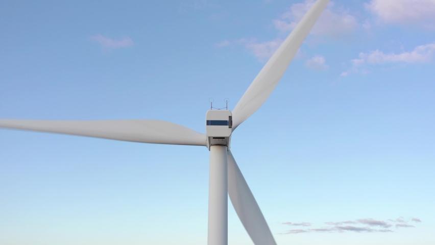 Aerial shot behind a big wind turbine revealing a rural community beneath. | Shutterstock HD Video #1060526353