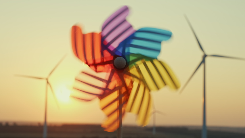 Pinwheel rotate color plastic, windmill blowing wind against  of wind turbines wind park sunset sky of sunny day summer. Descending bright disk of sun beyond horizon on field. Alternative energy Royalty-Free Stock Footage #1060527745