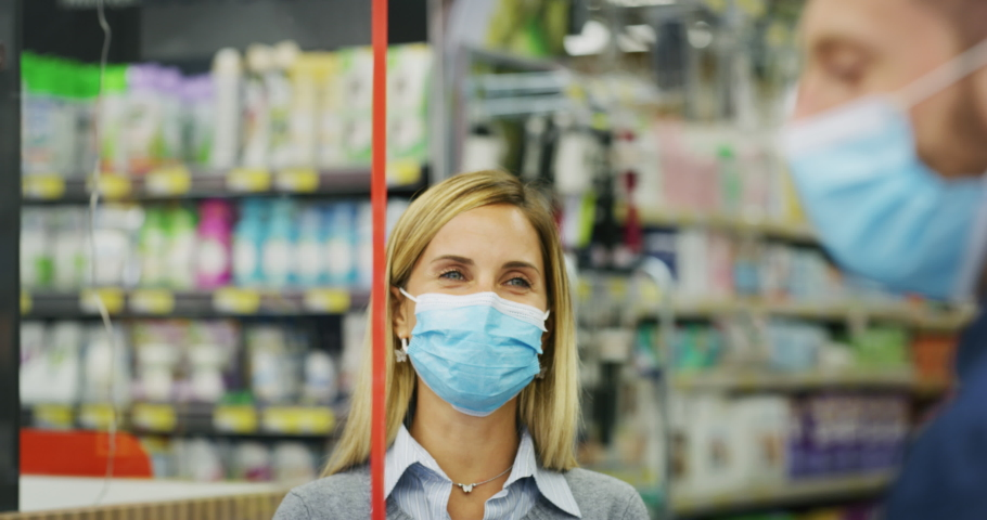 Authentic shot of female customer and male cashier wearing medical masks to protect themselves from disease while paying with credit card grocery food products in supermarket. Royalty-Free Stock Footage #1060528282