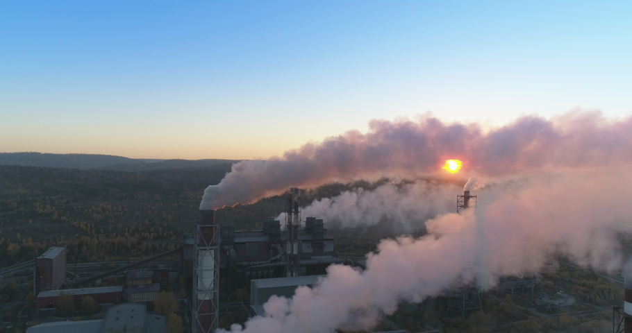 Aerial drone footage of steel factory pipes during sunset time. high above metallurgical plant and smoke cloud is coming from chimney. Aerial 4K | Shutterstock HD Video #1060529863