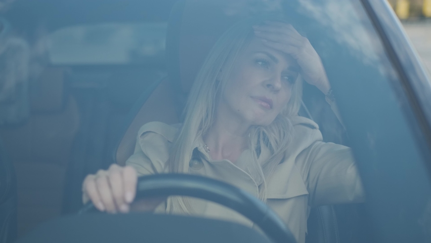 The stressed woman driver is sitting inside her car. Sad business woman is having headache has to make a stop after driving car in traffic jam on rush hour. Exhausted, overworked driver concept. | Shutterstock HD Video #1060529971