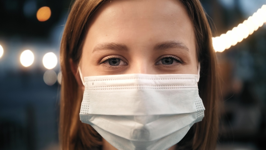 Close up portrait of caucasian young woman in medical mask standing at outdoor. Smiling person takes off mask. Healthcare. Safety measures concept. End of pandemic.