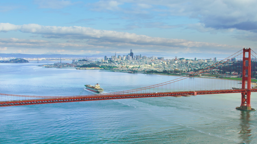 Aerial view of the magnificent Golden Gate Bridge with a cargo ship passing under it. This bridge connects the San Francisco peninsula to Marin County. US route 101 and SR 1 full of cars. Red 8K.