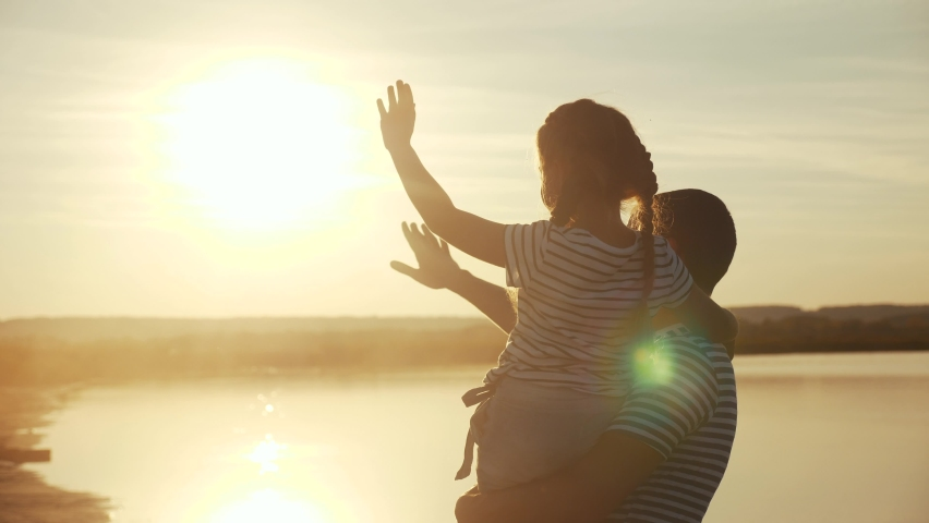 Happy family dad and daughter by the sea at sunset silhouette. father and child kid reach out to the sun. kid dream concept. happy family little girl and dad alone with nature relax sunset concept
