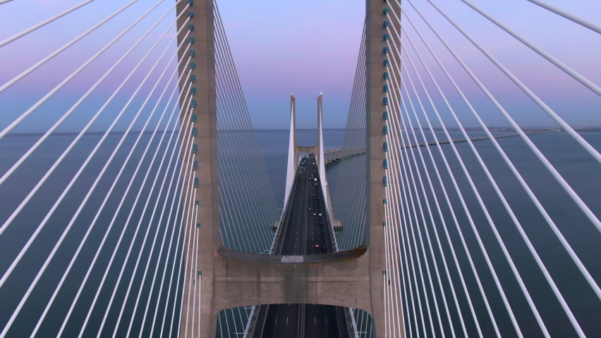 Aerial view of architectural landmark Vasco da Gama Bridge over the Tagus River at dusk in Lisbon, Portugal. The Vasco da Gama Bridge is the longest bridge in the European Union. Royalty-Free Stock Footage #1060541395