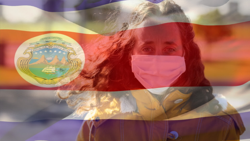 Animation of Costa Rican flag waving over mixed race woman wearing face mask, looking at the camera. Covid-19 coronavirus national health safety concept digital composite | Shutterstock HD Video #1060541479