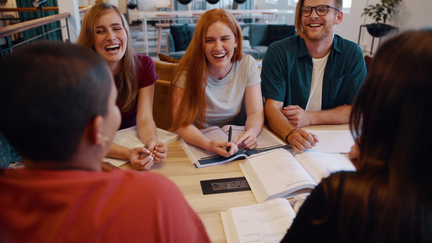 Group of students studying together in the college library and smiling. Classmates smiling during group study on the university campus. Royalty-Free Stock Footage #1060545187