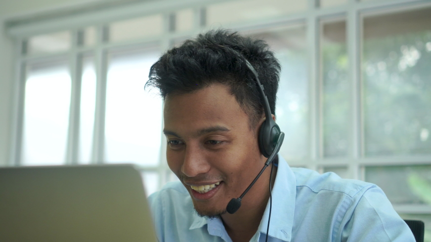Close up call center latin man wear a headset to talking with a customer and working at computer desktop in operation room for helpline and telesales service desk support concept.