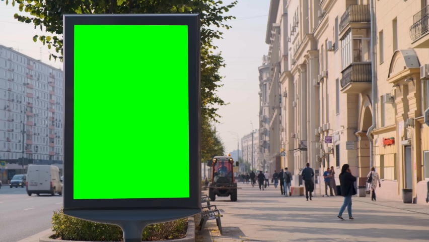 Green screen billboard located on a busy street. Cars move in a stream. Working day morning. People walk along the sidewalk. Cleaning equipment is working