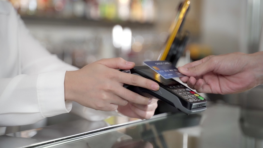 "A ""Dummy"" credit card is used to make a payment in a nice bright store. The customer reaches out to scan the card on the credit card machine by herself with no contact with the seller.  Royalty-Free Stock Footage #1060553125"