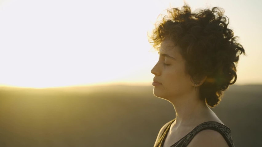 Close up young woman relaxing peacefully with beautiful desert sunset or sunrise. Concentrated in meditation and deep thoughts she quietly moves her head to clear mind and soul. Practice routine.   Shutterstock HD Video #1060557577