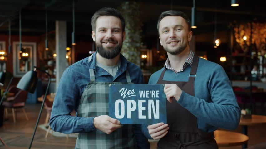 Portrait of cheerful young men in aprons business partners holding we are open sign standing in modern cafe together. Catering and start-up concept.