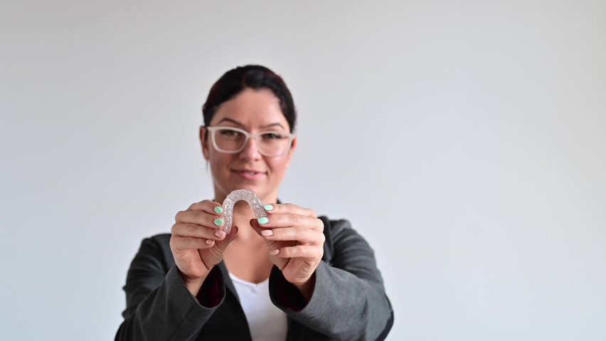 The woman is smiling and holding a transparent plastic aligner for bite correction Royalty-Free Stock Footage #1060563328