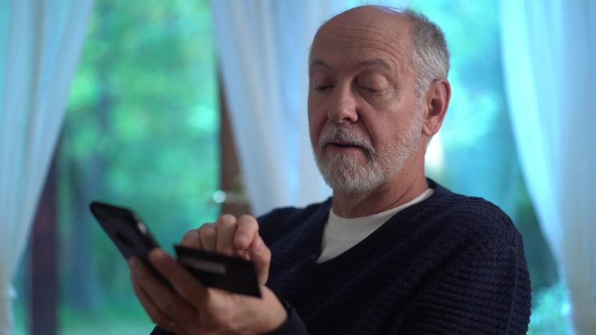 Extreme closeup of mature man using credit card to make purchase on smartphone online, typing in account number, with glass of wine. Royalty-Free Stock Footage #1060575553