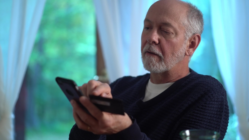 Extreme closeup of mature man using credit card to make purchase on smartphone online, typing in account number, with glass of wine. Royalty-Free Stock Footage #1060575556