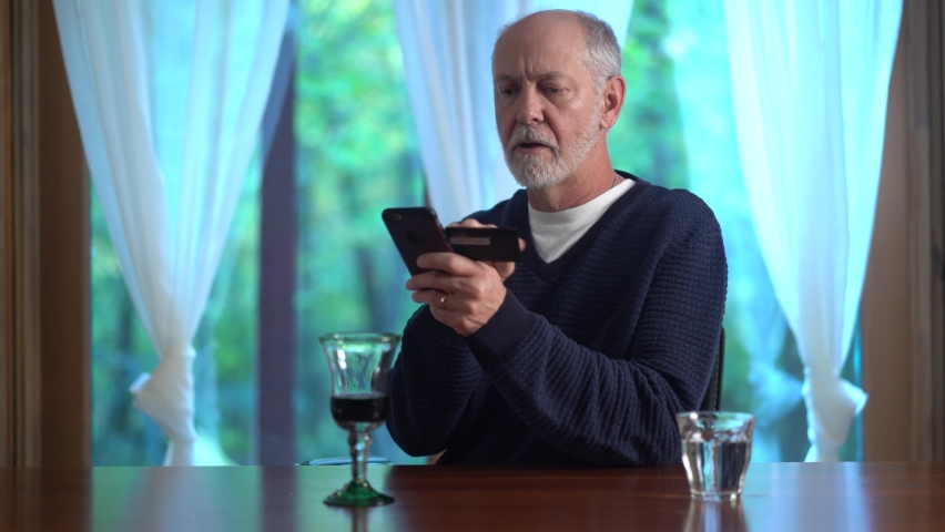 Wide shot of mature man using credit card to make purchase on smartphone online, typing in account number, with glass of wine. Royalty-Free Stock Footage #1060575568