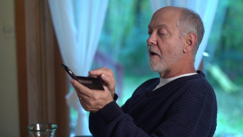 Turning closeup of mature man using credit card to make purchase on smartphone online, typing in account number, with glass of wine. Royalty-Free Stock Footage #1060575571