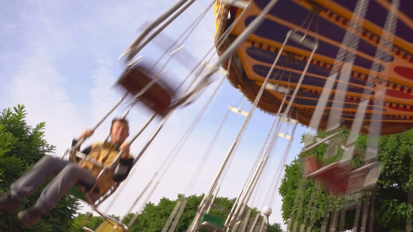 the carousel of the chain is spinning in the amusement Park. family ride a swing at a fun weekend fair or festival with their children. strolls. Royalty-Free Stock Footage #1060577917