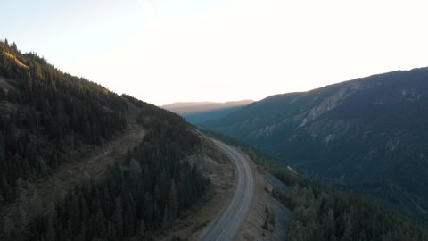 Aerial drone footage of rugged mountain peak next to Trans Canada highway at sunrise, 4K 24FPS.