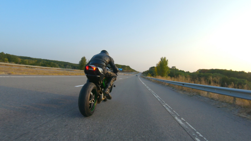 Biker is driving motorbike during road trip at autumn sunset time. Man ride fast on modern sport motorcycle at highway. Motorcyclist racing his bike on country road. Concept of adventure. Aerial shot Royalty-Free Stock Footage #1060581247