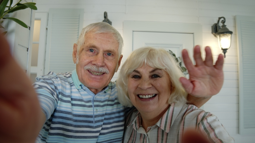 Mature man, woman making selfie, waving hands, showing thumbs up. Senior elderly caucasian couple using mobile phone for video call in porch at home. Talking on webcam. Social media network on phone