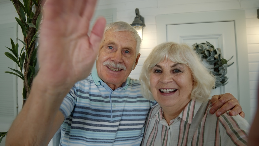 Mature man, woman making selfie. Senior elderly caucasian couple using mobile phone for video call in porch at home. Talking on webcam, waving hand. Social media network on phone. 6k downscale