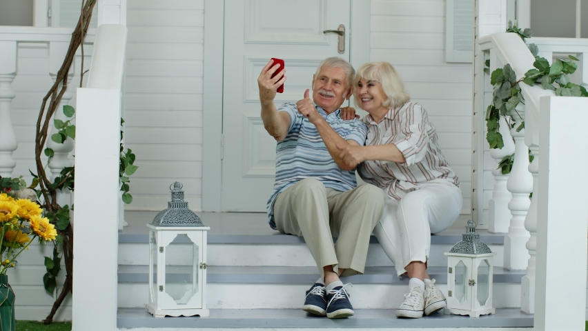 Senior elderly caucasian couple sitting, using mobile phone for video call in porch at home. Talking on webcam. Chatting, social media network on phone. Mature man, woman making selfie. 6k downscale
