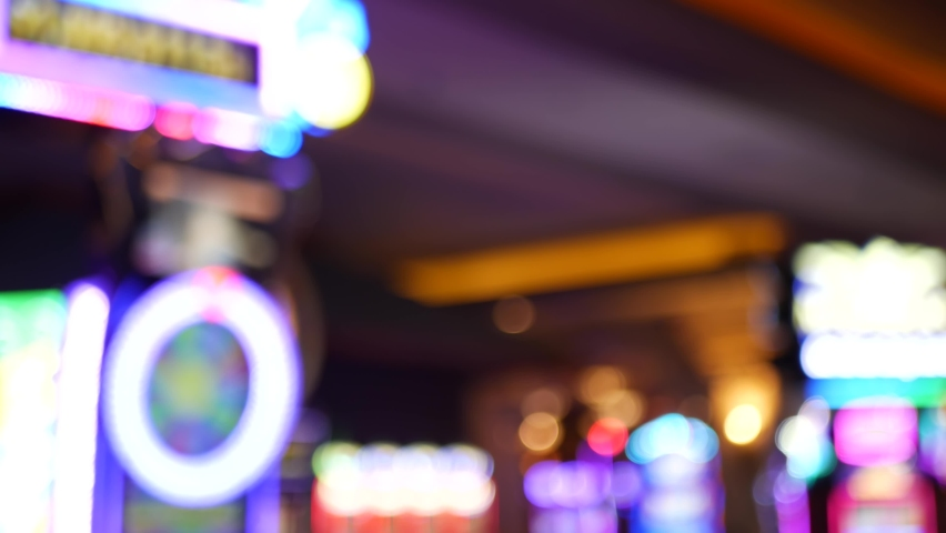 Defocused slot machines glow in casino on fabulous Las Vegas Strip, USA. Blurred gambling jackpot slots in hotel near Fremont street. Illuminated neon fruit machine for risk money playing and betting. | Shutterstock HD Video #1060590118