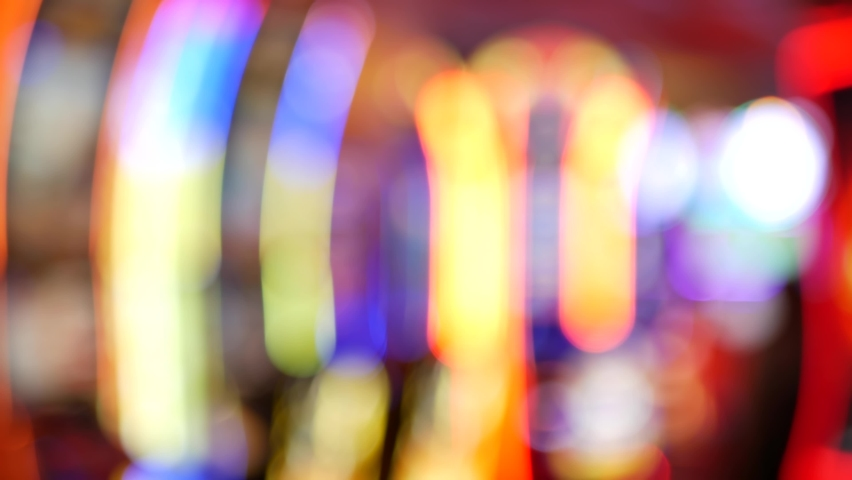 Defocused slot machines glow in casino on fabulous Las Vegas Strip, USA. Blurred gambling jackpot slots in hotel near Fremont street. Illuminated neon fruit machine for risk money playing and betting. | Shutterstock HD Video #1060590205