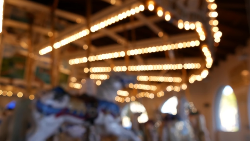 Golden illuminated defocused retro carousel turning in amusement park. Blurred shiny merry-go-round glowing and rotating at night. Radiant spinning symbol of childhood. Festival atmosphere of funfair. Royalty-Free Stock Footage #1060590223