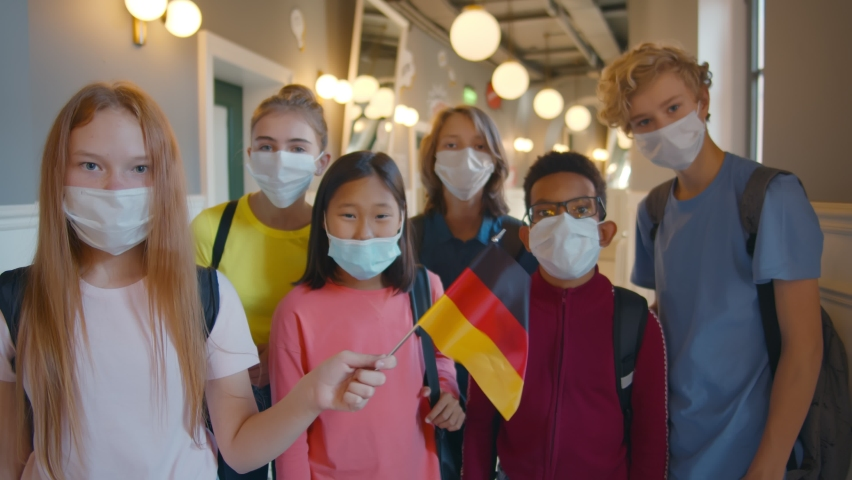 Diverse school students in mask standing in corridor holding german flag. Schoolgirl waving german flag with classmates standing on background. International pupils in protective mask | Shutterstock HD Video #1060591648
