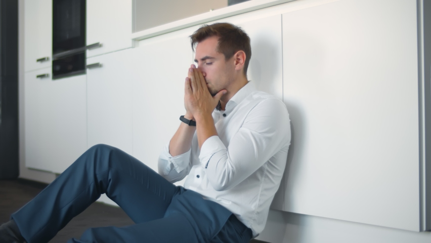 Depressed young businessman sitting on floor in kitchen. Portrait of anxious handsome man on kitchen floor having business or personal problems feeling stressed and desperate