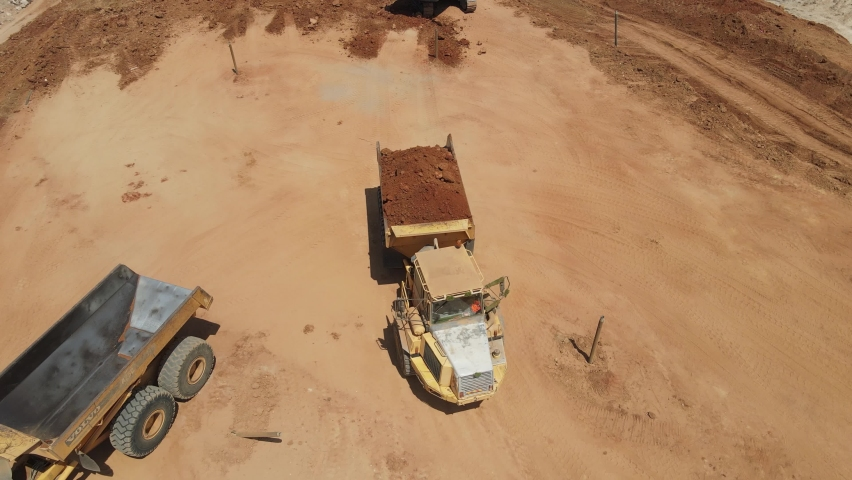 Aerial view of heavy machinery, Articulated truck moving dirt on a new road construction site, heavy equipment top down footage of dump truck