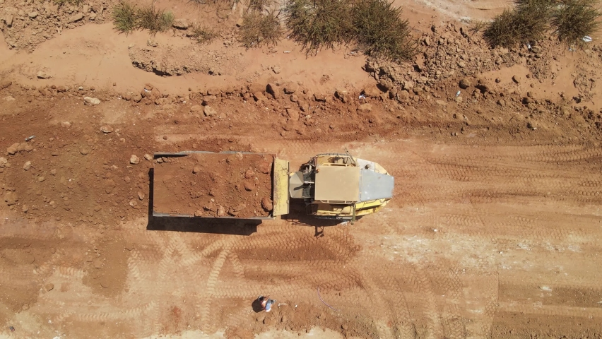 Aerial view of heavy machinery, Articulated truck unloading dirt on a new road construction site, heavy equipment top down footage of dump truck