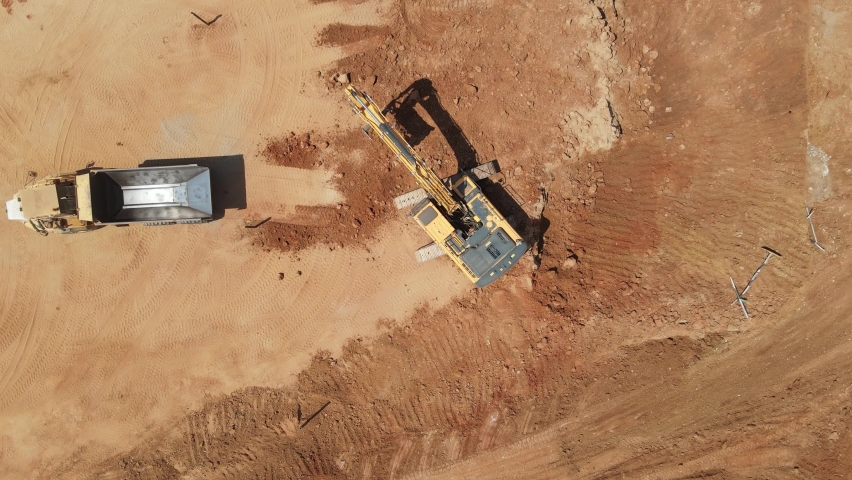 Aerial view of heavy machinery, excavator scoop loads a  articulated truck, heavy equipment top down footage