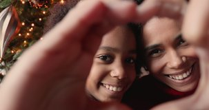 Close up African mom and daughter faces view through heart shape joined fingers, vloggers share love congratulate subscribers Merry Christmas. New Year celebration, happy holidays, best wishes concept