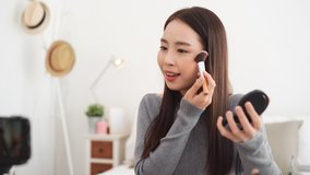 Young beautiful Asian woman professional beauty vlogger influencer recording make up tutorial video clip at home for social media marketing