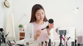 Young beautiful Asian woman professional beauty vlogger influencer recording make up tutorial video clip in bedroom at home for social media marketing