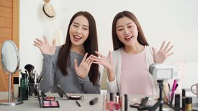 Pretty Asian female friend beauty influencers greeting the audiences while recording viral video clip with camera at home