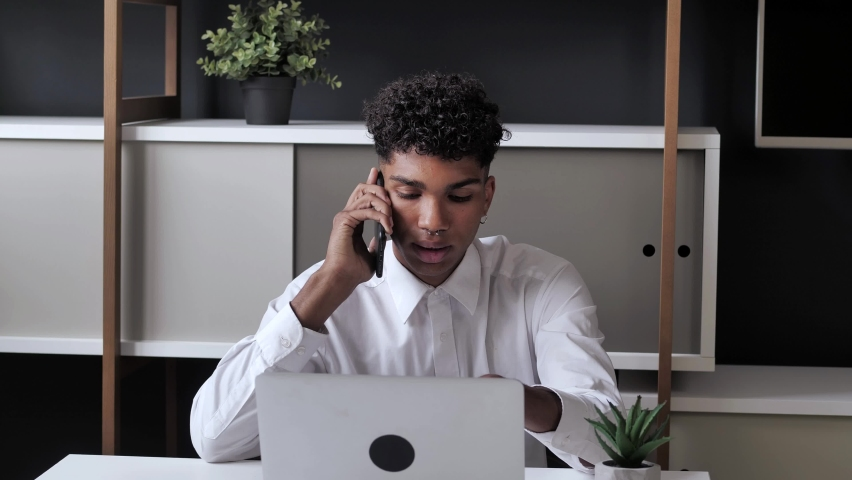 Smiling young black man professional talking on phone using laptop sit at modern office desk, serious male customer make mobile call confirming online website shopping order delivery concept 4