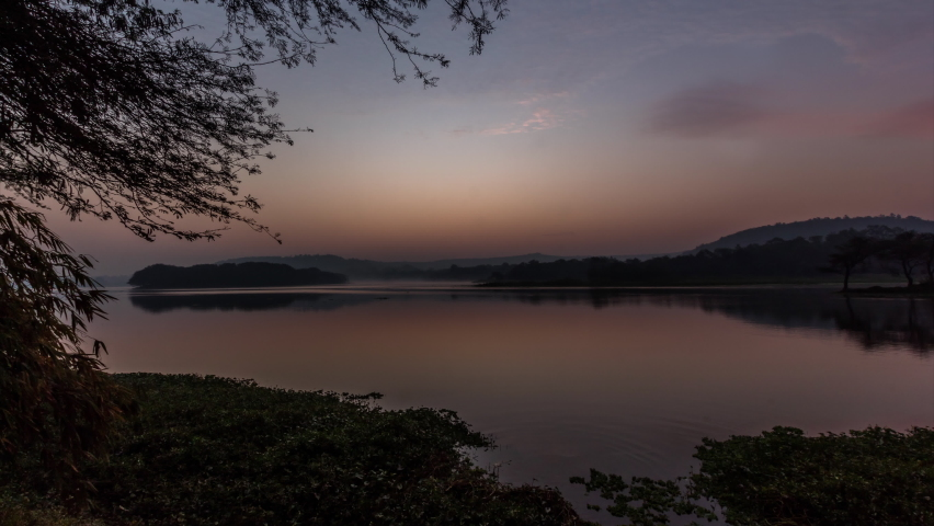 4k Time lapse of Sunrise over a lake with Reflection of Clouds and sun in Lake Water Surrounded by Grass, Trees and Hills, Pune City, India