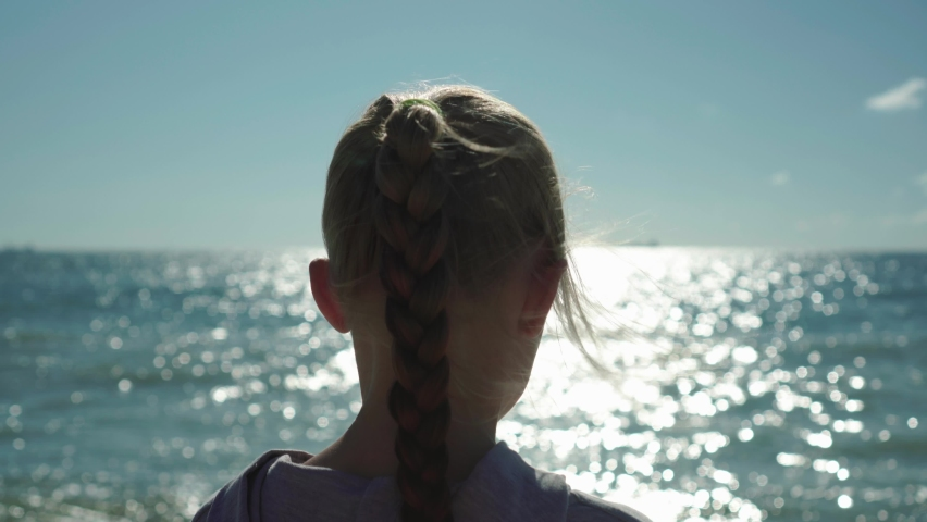 Close up of blonde child girl with a braid she looks at the sea water sparkling with shimmering lights at sunset. Wind in her hair. She is dreaming of future   Shutterstock HD Video #1060598086